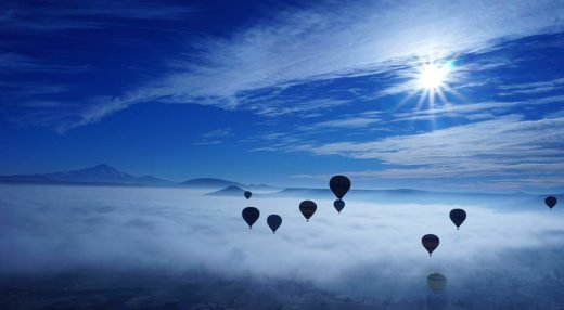 Hot air balloons rising amidst the clouds.